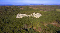 Felsenformation in Branzez, in Hintergrund verschneites Riesengebirge - im Märzz